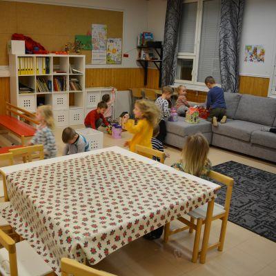 Päiväkotilapset leikkivät koululuokassa.
