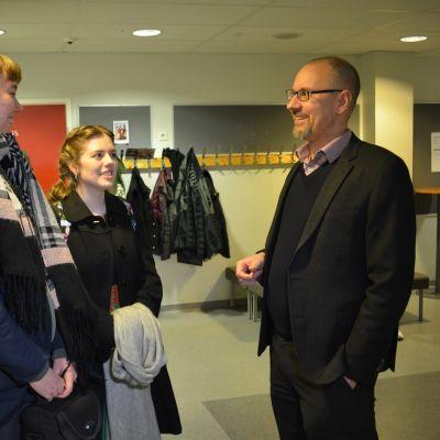 Kaksi abiturienttia, Sini Ojala ja Tiara Visser sekä apulaisrehtori Sami Peltonen keskustelevat koulun käytävällä.