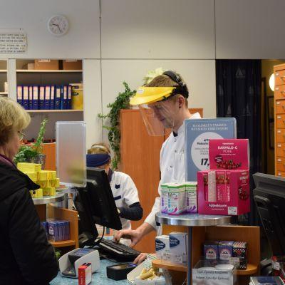 Farmaceut Micael Qvarnström iförd skyddsvisir betjänar en kund.