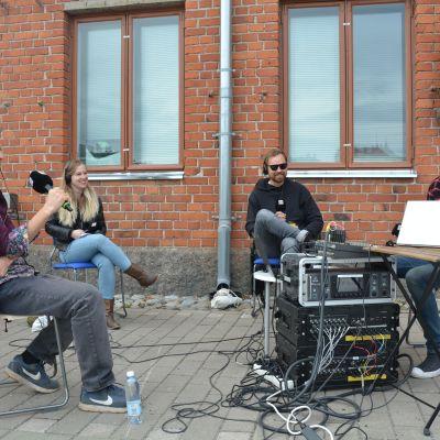 Kulturjournalisten Tomas Jansson, Viper Arms basist Soffe, Sivujuttus sångare Martin Laine och redaktören Joakim Rundt sitter på stolar framför en tegelvägg i en direktsändning om rockmusiken i Åbo.