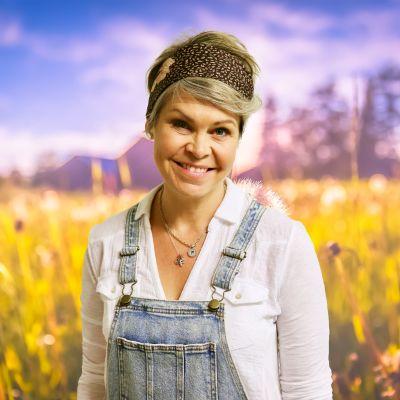 Nina Brännkärr-Friberg står på en sommaräng och ler mot kameran.