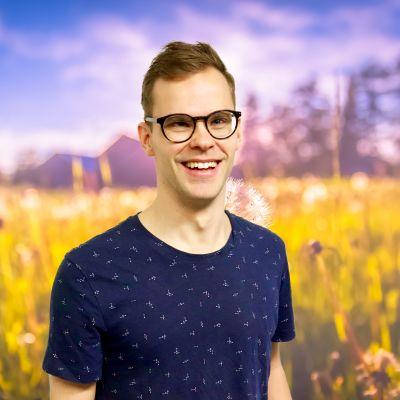 Alaric Mård ler stor rakt in i kameran från en sommaräng.