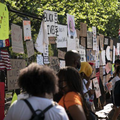 Människor och plakat vid staketet runt Vita huset i Washington.