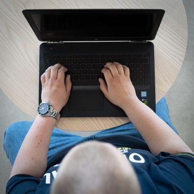 Nuori mies näpyttää tietokonetta.
