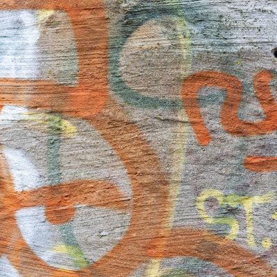 Graffittteja muuratussa seinässä.