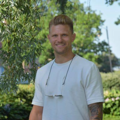 En man med kort blont hår och vit t-skjorta står ute vid en park. Det är Stallörsparken i Ekenäs och det är sommar och sol. Han tittar rakt in i kameran och ler