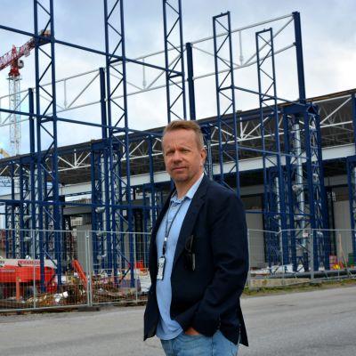 Man i kavaj står framför en byggarbetsplats.