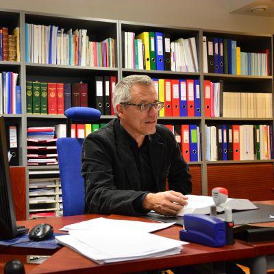 Man med grått hår och glasögon klädd i svart skjorta sitter framför en bokhylla fylld av pärmar.