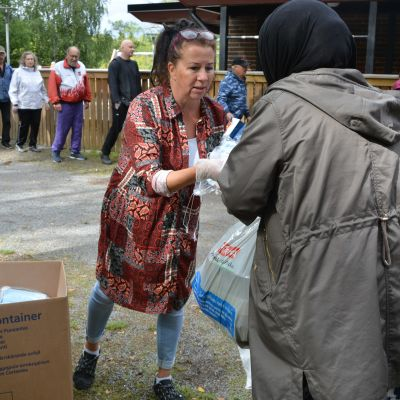 Muslimsk kvinna får munskydd av frivilligarbetare i brödkö.