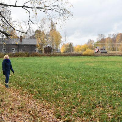 Suomalainen maisema, jossa rakennus ja vaaleahiuksinen nainen