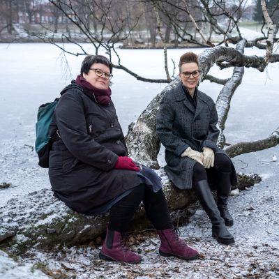 Kaksi yliopistotutkijaa istumassa puunrungolla.