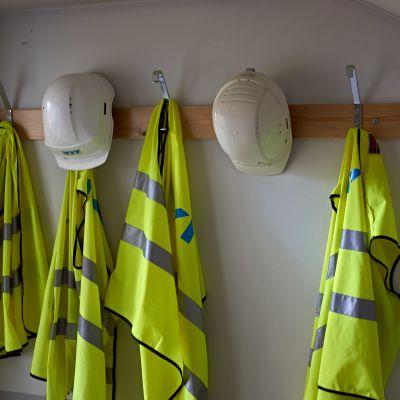 Rakennustyömaa, turvaliivejä ja kypäriä naulakossa