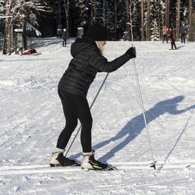 Nuori nainen opettelee hiihtämään Paloheinän hiihtoladulla.