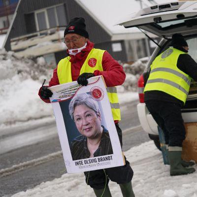 Henkilö kantaa vaalijulistetta, taustalla toinen nostaa julisteita auton peräkontista