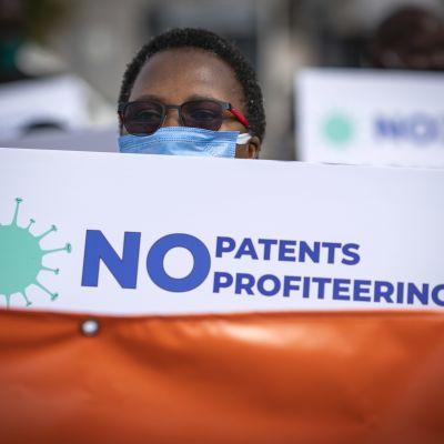 """En demonstrant håller upp ett plaket med texten """"No Patents profiteering"""""""