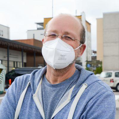 Kimmo Huima i vitt munskydd och blå huppare utomhus.