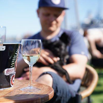 En man sitter på en uteservering med öl framför sig.