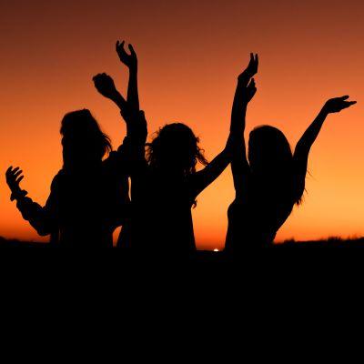 Tre dansande silhuetter mot orange bakgrund