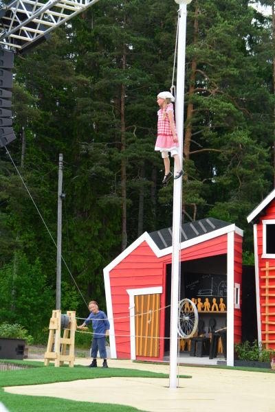 Emil hissar upp Ida i flaggstången.