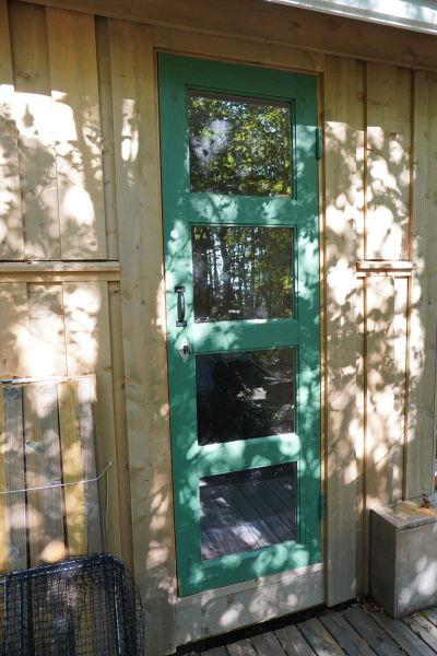 En del av ett uthus med obehandlad träpanel på ytterväggen och en grön dörr med glasspeglar.