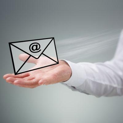 """En illustrativ bild av en hand som håller i ett """"elektronsikt"""" kuvert med @-symbolen på."""