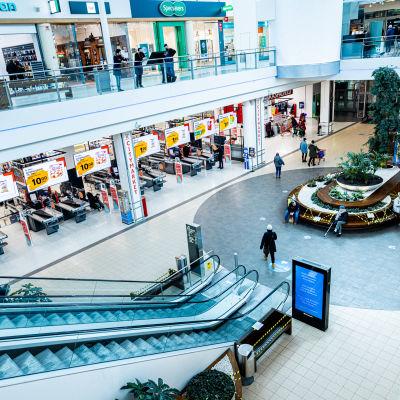 Köpcenter som ser ganska öde ut, men bara en handfull människor som syns på bilden.