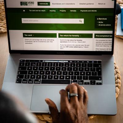 En person sitter framför en laptop med Skatteförvaltningens webbsida öppen.