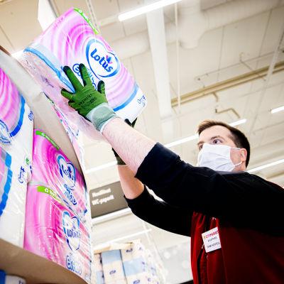 Kauppias Sami Hertell järjestelee vessapaperilavoja.