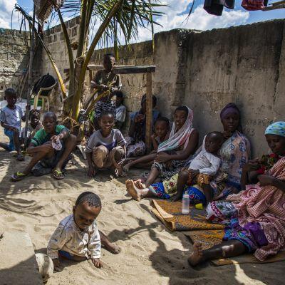 Ihmisiä istumassa maassa, edessä leikkii sylilapsi