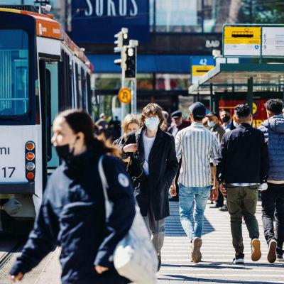Personer med munskydd i Helsingfors centrum. Bilden är tagen i maj 2021.