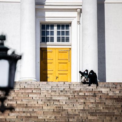 Två personer med munskydd sitter på Domkyrkan trappa i Helsingfors.