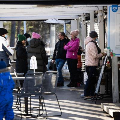 Ihmisiä jonottaa kahvila-ravintolan ulkoluukulla tilatakseen.