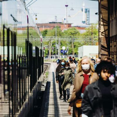 Tågpassagerare med munskydd på i Helsingfors.