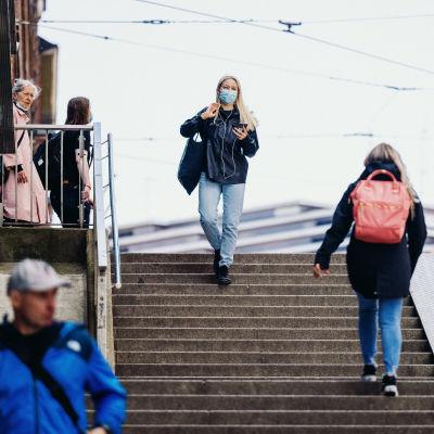 En kvinna med munskydd går ner för en trappa i Helsingfors centrum.