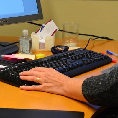 En person jobbar vid en dator.