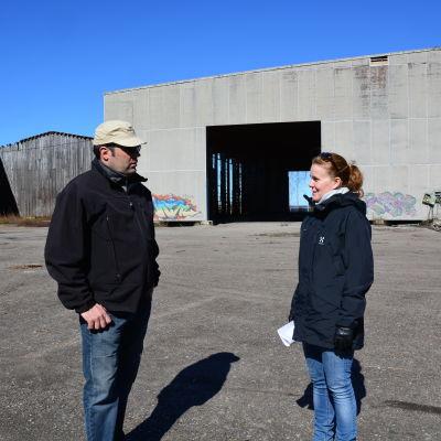 Båtföretagare Johan Hammarström och markanvändningsingenjör Annika Birell framför en gammal hall som nu ska bli båthall.