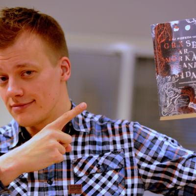"""Kaj Korkea-Aho med sin bok """"Gräset är mörkare på andra sidan"""""""