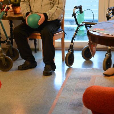 Äldre man deltar i sittgymnastik