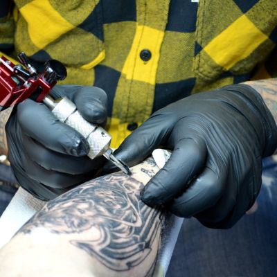 Dag Bäcklund använder tatueringsmaskin.