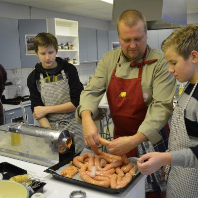 Kökschef Kenneth Löfberg instruerar högstadieeleverna Tomi Berg och Emil Lindholm i korvstoppningens ädla konst.