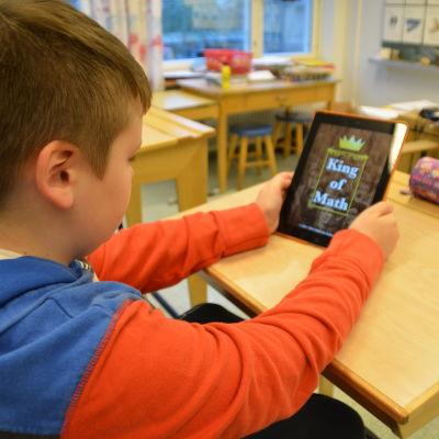 Pojke använder en pekplatta för att räkna matematik.