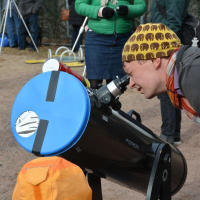 Marcus Alanen kollar in solförmörkelsen via en specialutrustuad stjärnkikare.