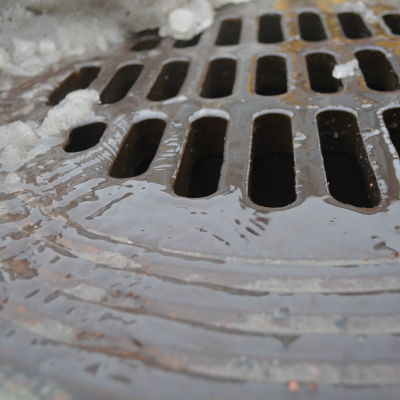 Smältvatten rinner ner i gatubrunn.