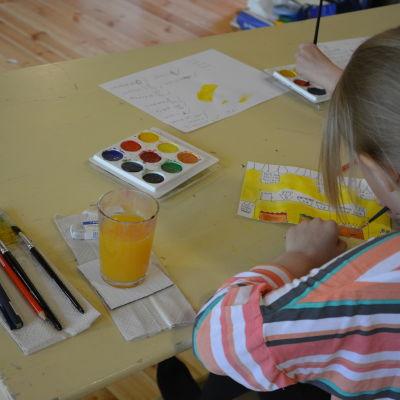 Flicka målar med vattenfärger.