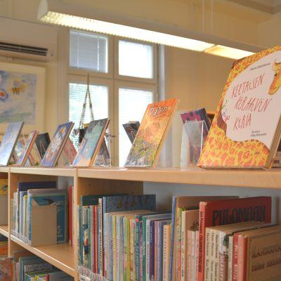 Böcker på rad i ett bibliotek.