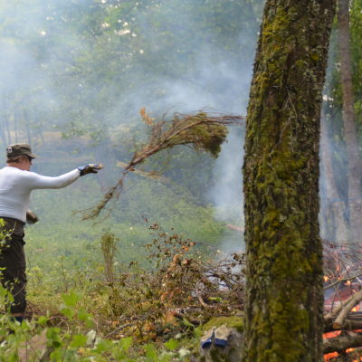 En deltgarare kastar ris på elden.