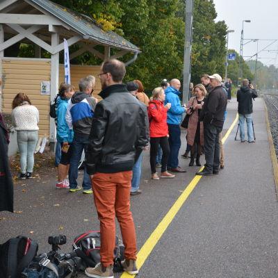 Människor står på en tågperrong, tågbana till höger, höstlöv på marken.