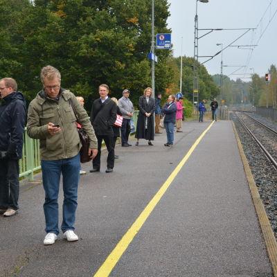 Människor står på en tågperrong, tågbana till höger.