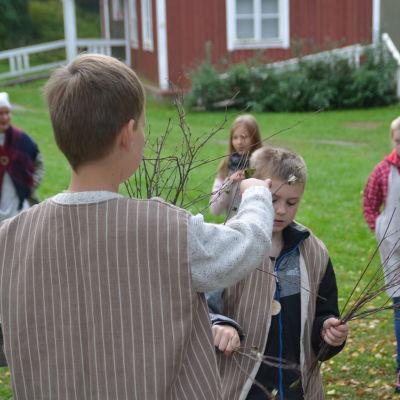 Pojkar från Merituulen koulu binder kvast på tidsresa vid Gammelgården i Ingå