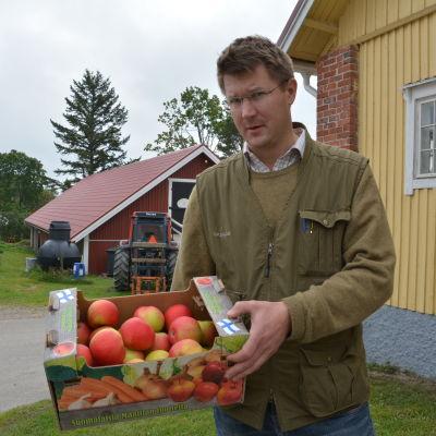 Mikael Jensen håller fram låda med äpplen.